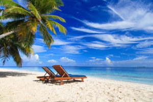 beach chairs in the pristine white sand alongs side the crystal clear waters on a sunny day