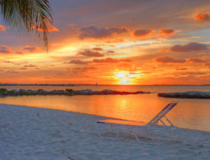 the sun sets on the horizon of a still ocean leaving a orange glow in the sky over the white beaches