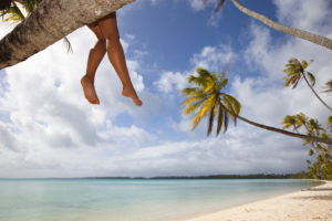 girl sitting on a palm tree dangling her feet over the sandy beaches of Long Island with aqua waters