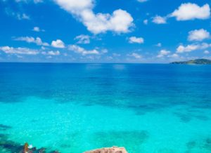 clear turquoise ocean in Bahamas with cloudy sunny skies
